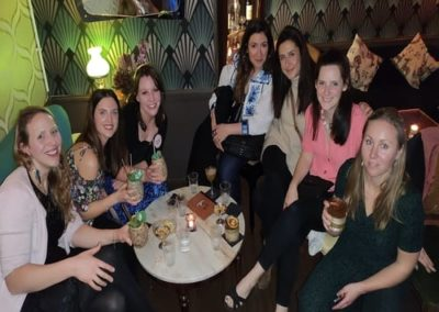 Group of girls sat down with cocktails